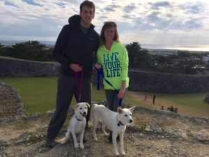 Couple standing on grass, overlooking historical stone ruins, with two white puppies on leashes.