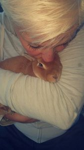 A woman cuddles a sweet bunny and gives it a kiss